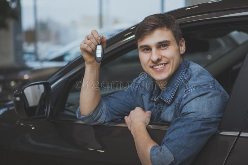 Handsome man choosing new automobile to buy. Excited young man smiling holding car keys, sitting in a new automobile at the dealership. happy man buying new car stock image