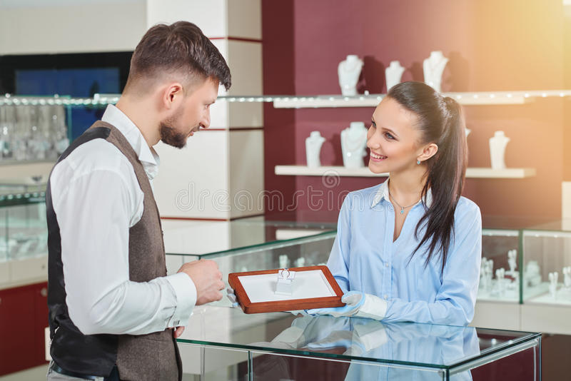Handsome man choosing ring with blue stone for girlfriend. stock image