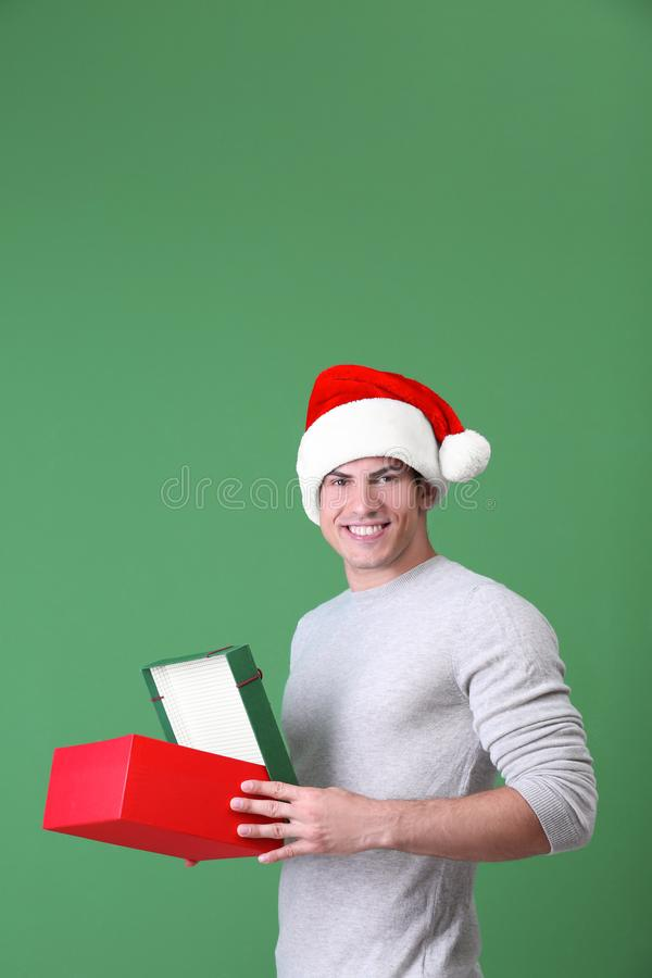 Handsome man in Christmas hat opening gift box. On color background royalty free stock photography