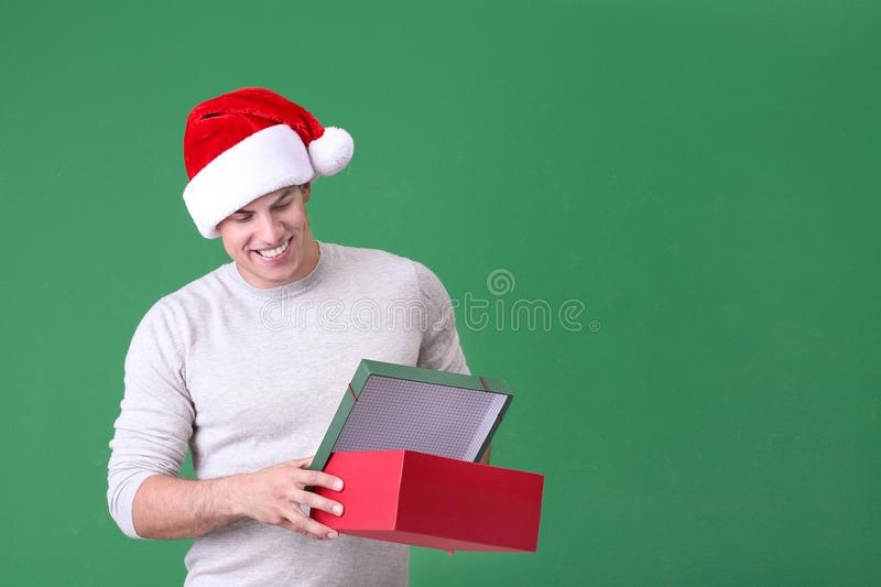 Handsome man in Christmas hat opening gift box royalty free stock image