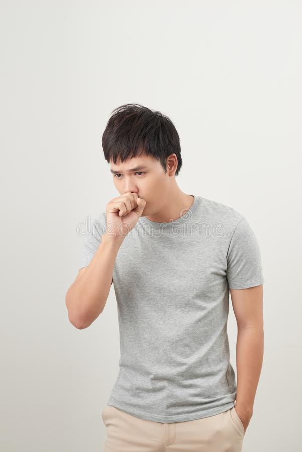Handsome man coughing into his fist, isolated on a white background.  stock photography