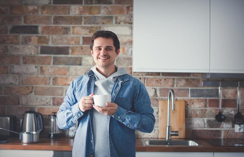Handsome man with cup of tea or coffee standing at kitchen stock images
