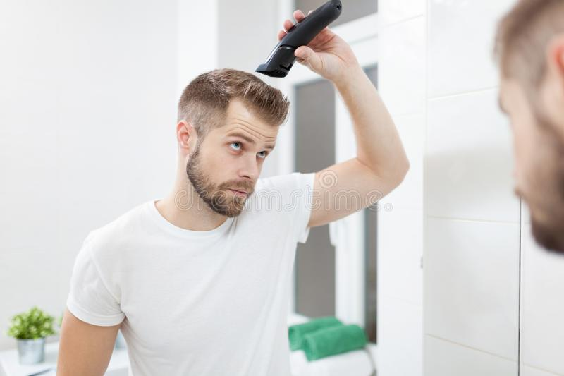 Handsome man cutting his own hair with a clipper stock images