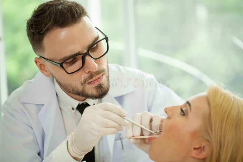 Handsome man dentist treats teeth of young woman patient with a stock photos