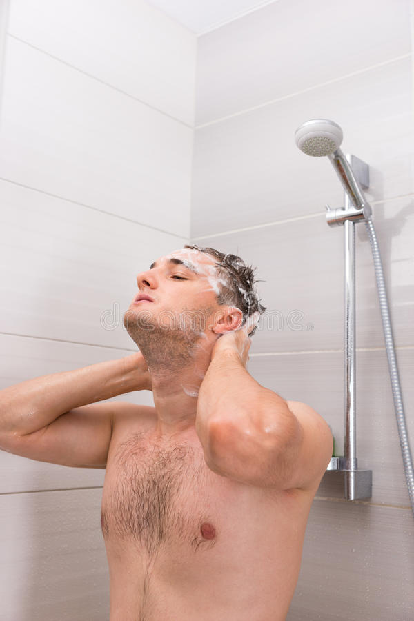 Handsome man diligently washing his hair in shower cabin in the stock photo