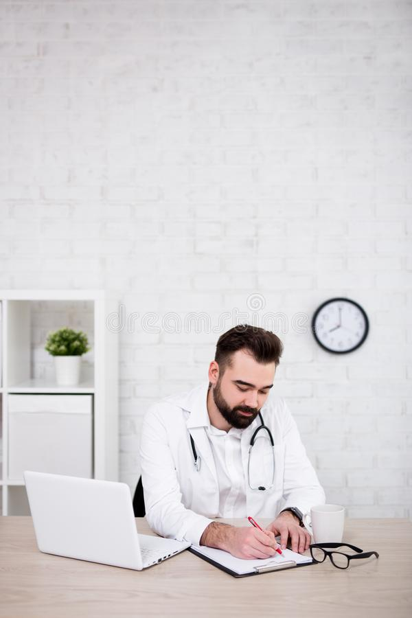 Handsome man doctor working in office - copy space over white brick wall stock photo