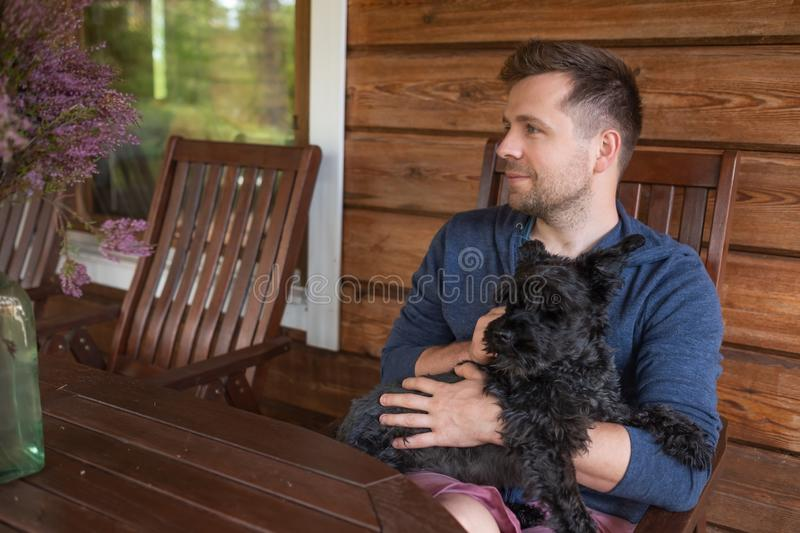 Handsome caucasain man with dog sitting outdoor royalty free stock photos