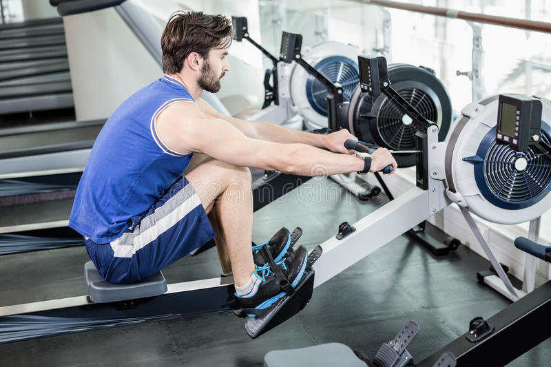 Handsome man doing exercise on drawing machine royalty free stock image