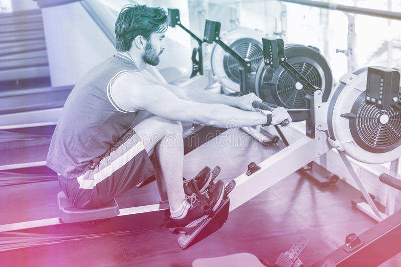 Handsome man doing exercise on drawing machine royalty free stock images
