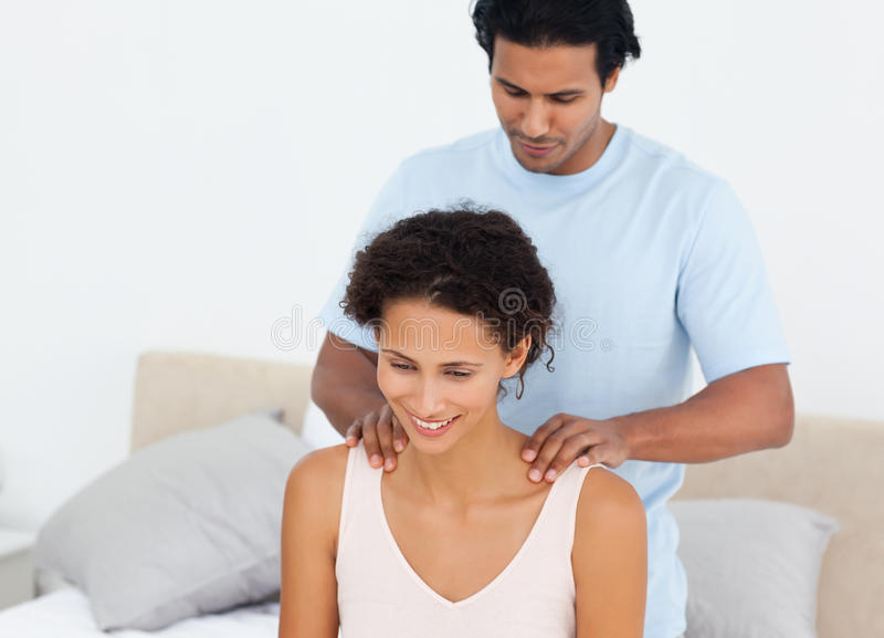 Handsome man doing a massage to his beautiful wife royalty free stock photography