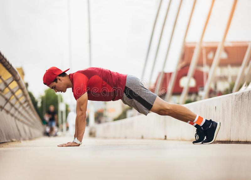 Handsome man doing push-ups outdoors on sunny day. Fitness concept royalty free stock images