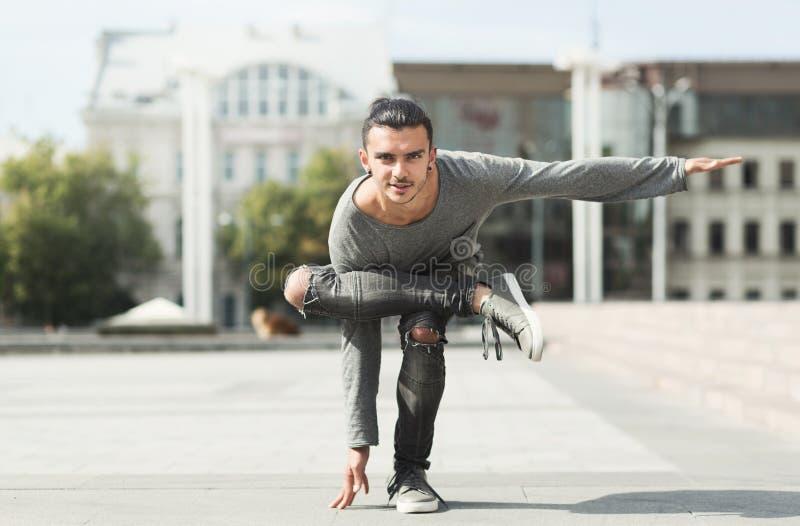 Handsome man doing yoga asana in urban area. Handsome man doing yoga asana outdoors in urban area royalty free stock photo