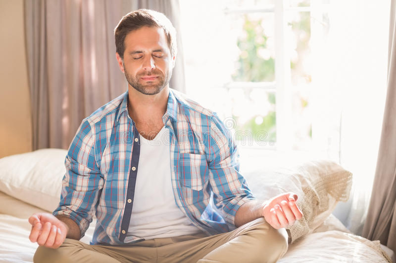 Handsome man doing yoga on his bed royalty free stock images