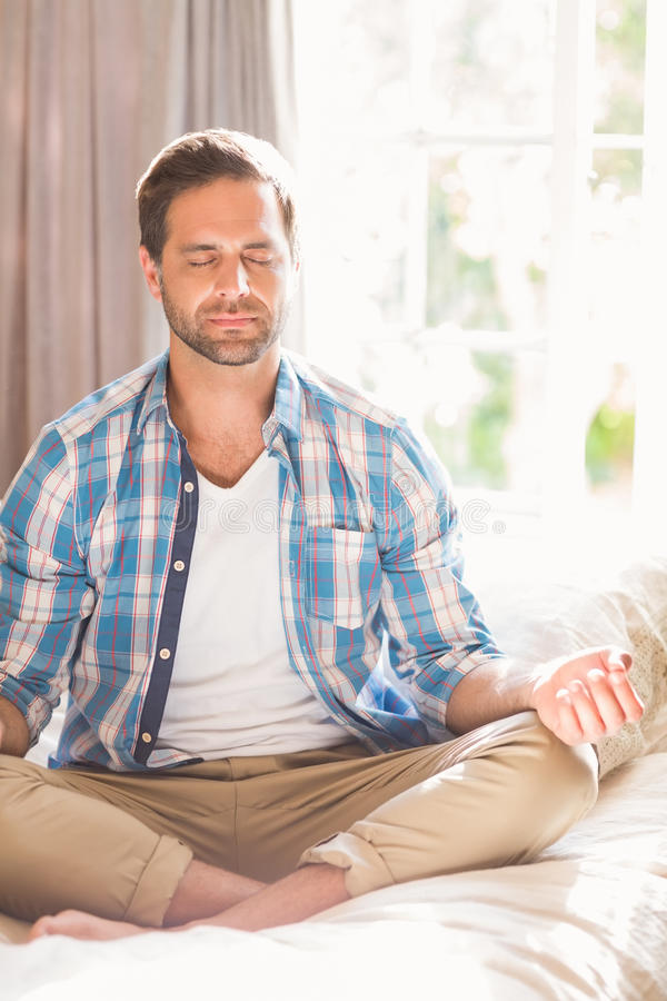 Handsome man doing yoga on his bed stock photo