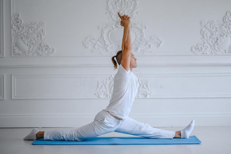 Handsome man doing yoga pose  on a white background royalty free stock photos