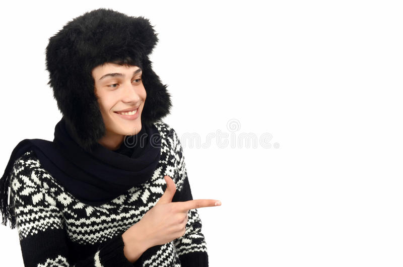 Handsome man dressed for a cold winter pointing in front smiling. royalty free stock image