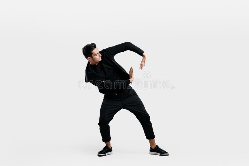Handsome man dressed in a stylish black clothes is dancing street dance. He makes stylized movements with his hands.  stock photos