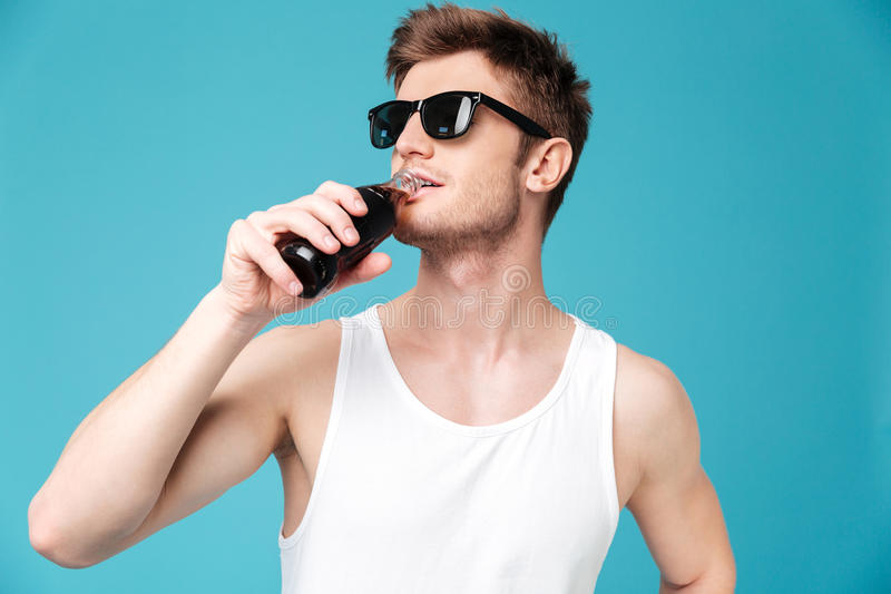 Handsome man drinking aerated sweet water. Photo of young handsome man standing over blue isolated background drinking aerated sweet water. Looking aside royalty free stock photos