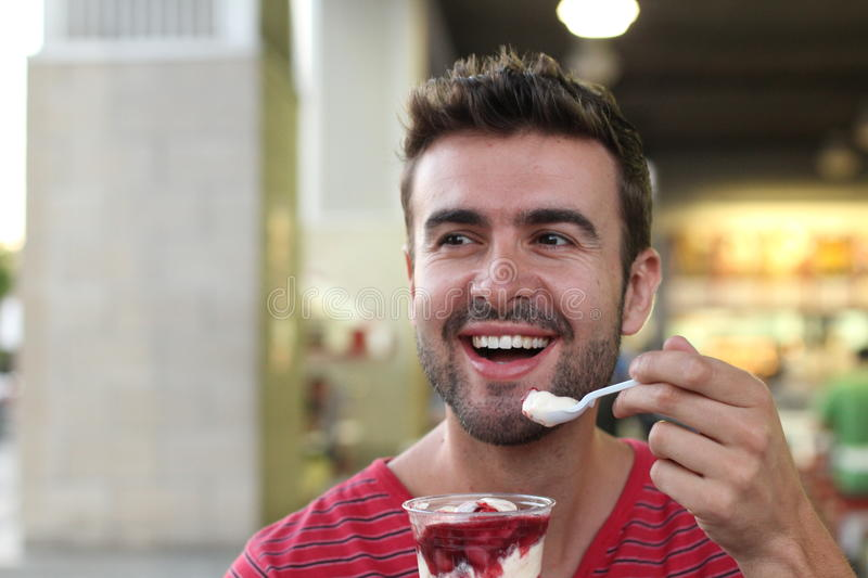 Handsome man eating a yummy ice cream.  stock photography