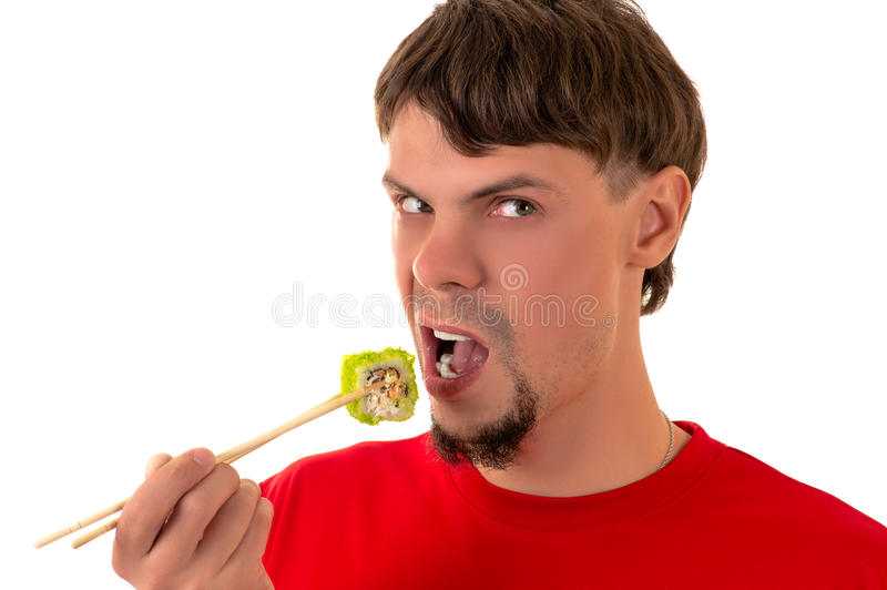 Handsome man emotionally eating sushi roll stock image