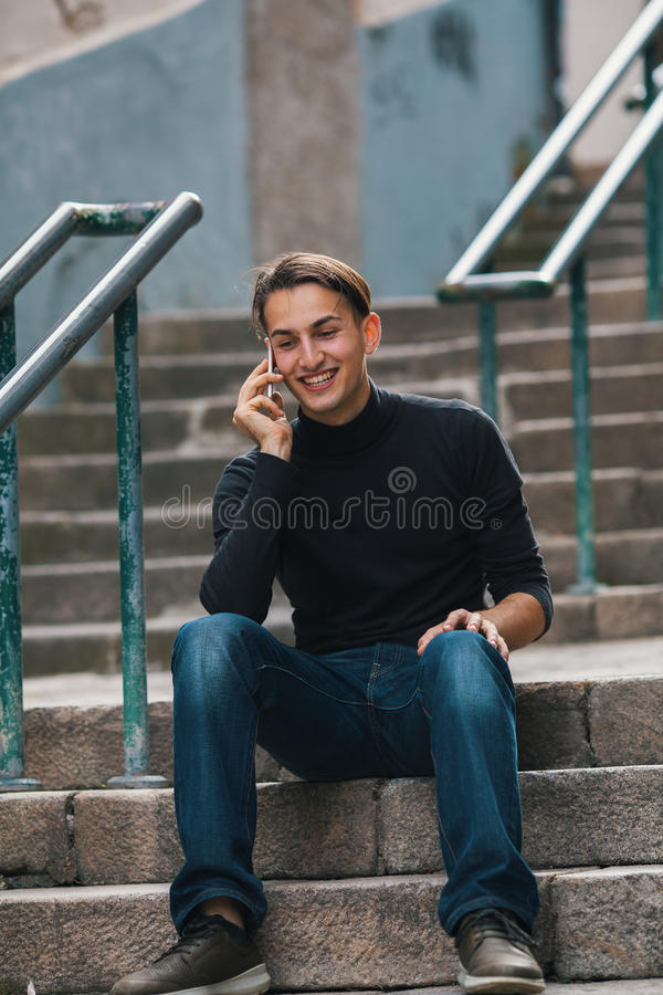 Handsome man emotionally talking on the phone sitting on stone steps in old european downtown. stock photos