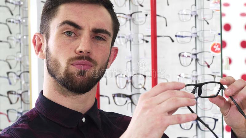 Handsome man examining pair of glasses at the optometrists store royalty free stock photography