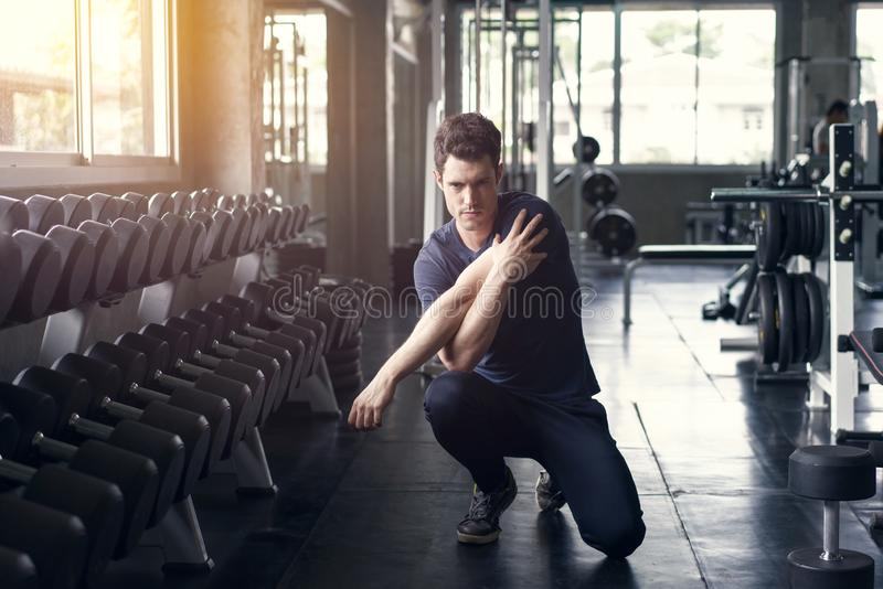 Handsome man exercise workout in gym fitness breaking relax and warm up with dumbbell for bodybuilding royalty free stock image