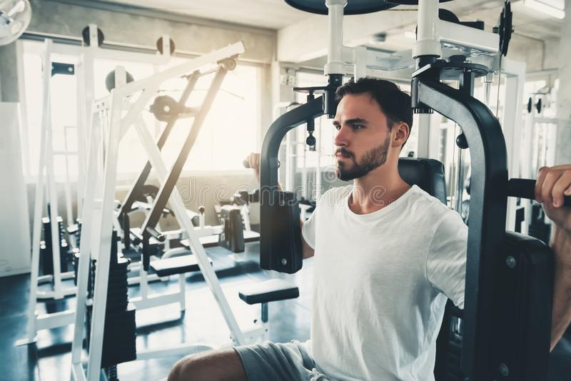 Handsome Man is Exercising With Pectoral Machine in Fitness Club.,Portrait of Strong Man Doing Working Out Calories Burning in Gym. Healthy and Fitness stock photography