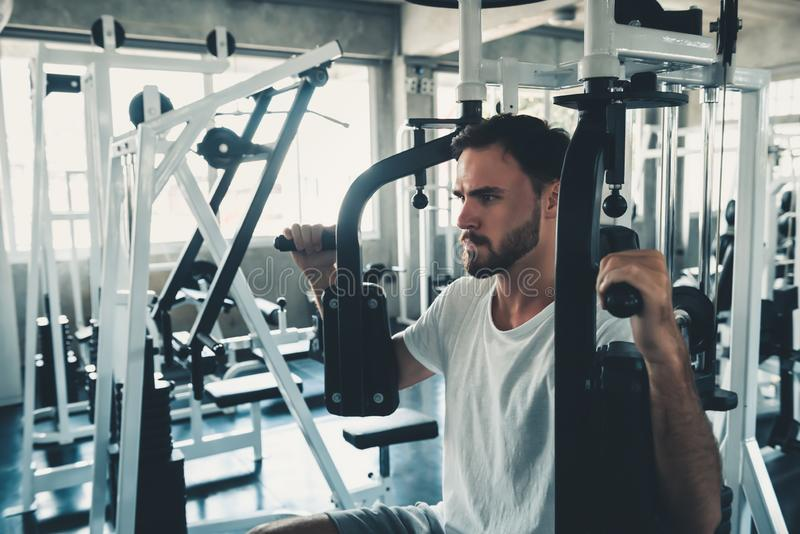 Handsome Man is Exercising With Pectoral Machine in Fitness Club.,Portrait of Strong Man Doing Working Out Calories Burning in Gym. Healthy and Fitness stock photo