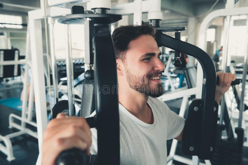 Handsome Man is Exercising With Pectoral Machine in Fitness Club.,Portrait of Strong Man Doing Working Out Calories Burning in Gym. Healthy and Fitness royalty free stock photos