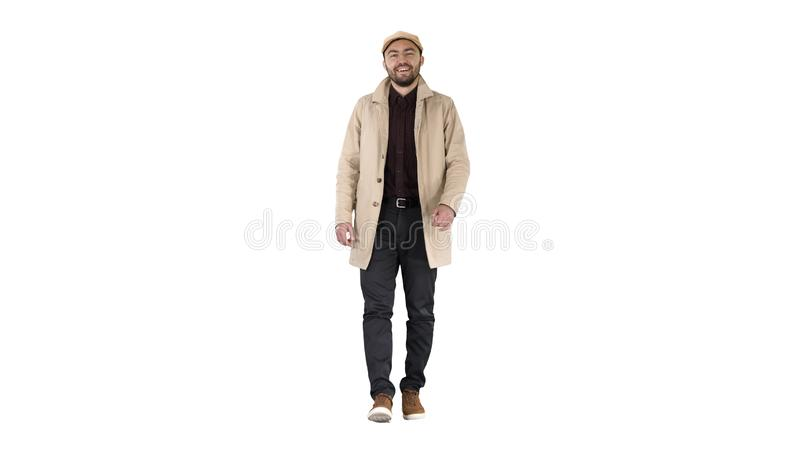 Handsome man in fashionable clothes walking and smiling on white background. royalty free stock image