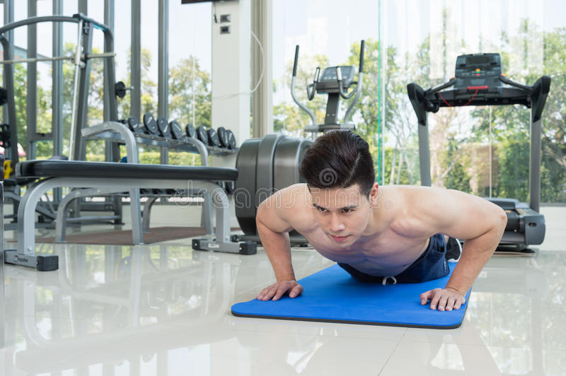 Handsome man fitness exercising by doing push ups as part of bod. Ybuilding training in the fitness center or gym, sport and health concept royalty free stock images