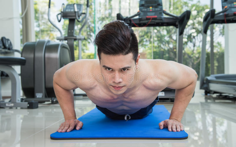 Handsome man fitness exercising by doing push ups as part of bodybuilding training in the fitness center or gym. Handsome man fitness exercising by doing push royalty free stock image