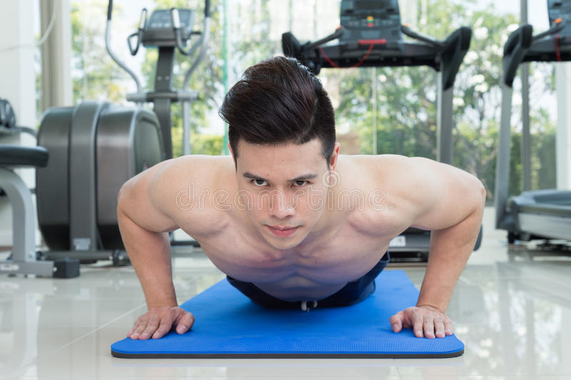 Handsome man fitness exercising by doing push ups as part of bodybuilding training in the fitness center. Or gym, sport and health concept stock photo