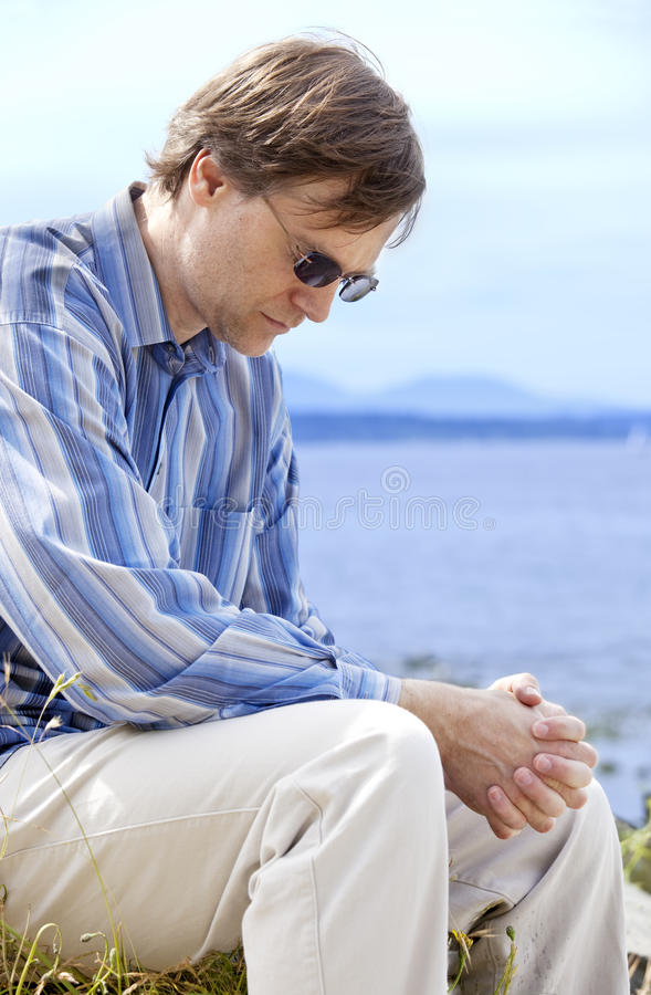 Handsome man in forties praying by side of lake