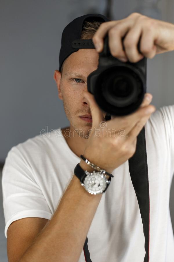 Handsome man with freckles holds a digital camera. And takes pictures. The concept of a young successful photographer royalty free stock photography