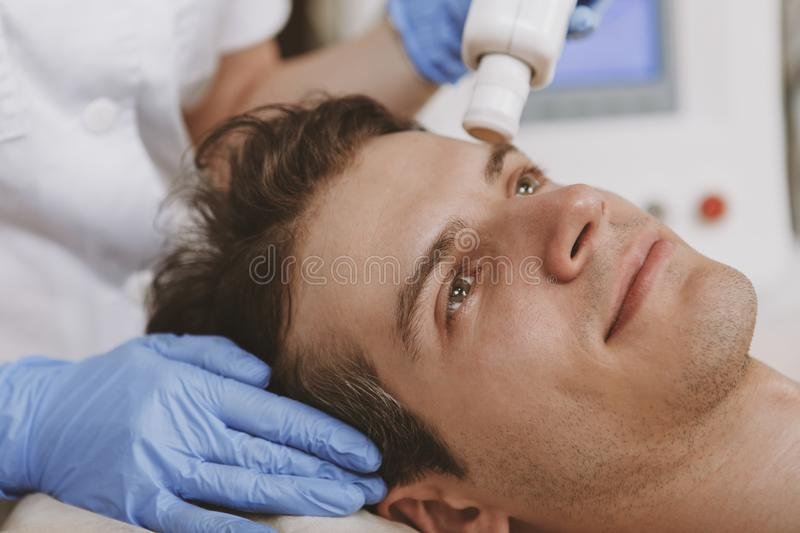 Handsome man getting facial skincare treatment stock images
