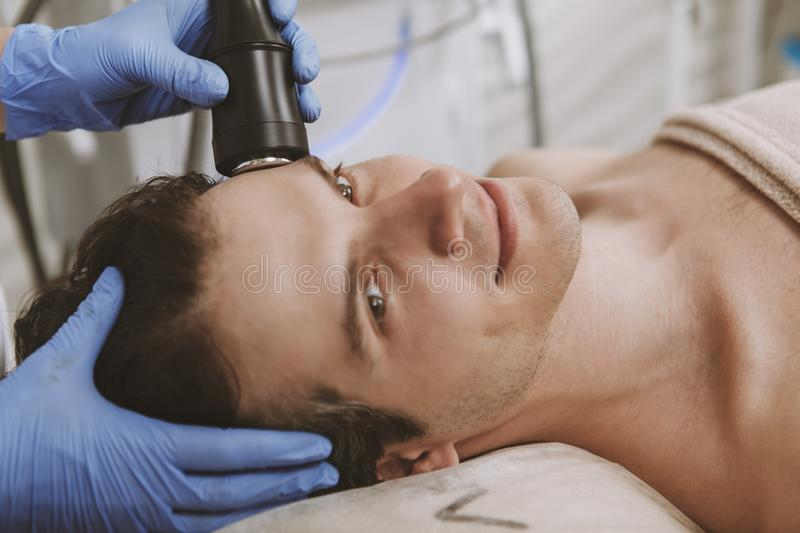 Handsome man getting facial skincare treatment stock photography