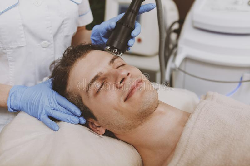 Handsome man getting facial skincare treatment royalty free stock photo