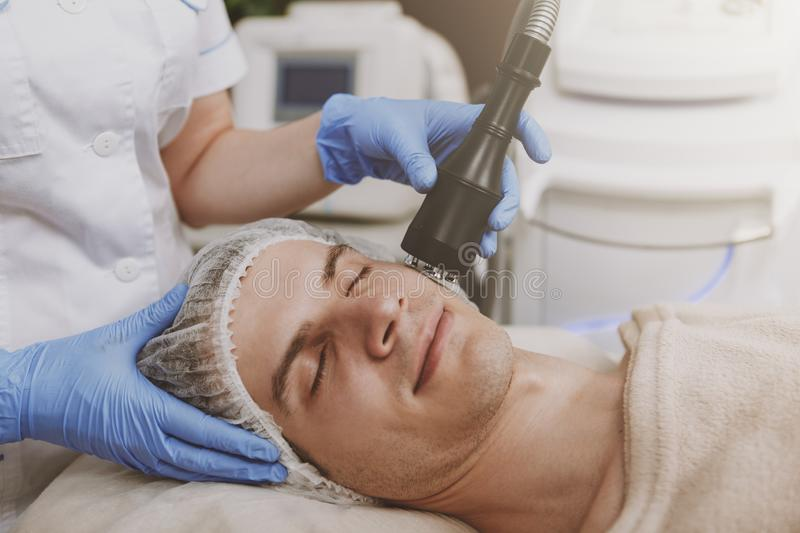 Handsome man getting facial skincare treatment royalty free stock images