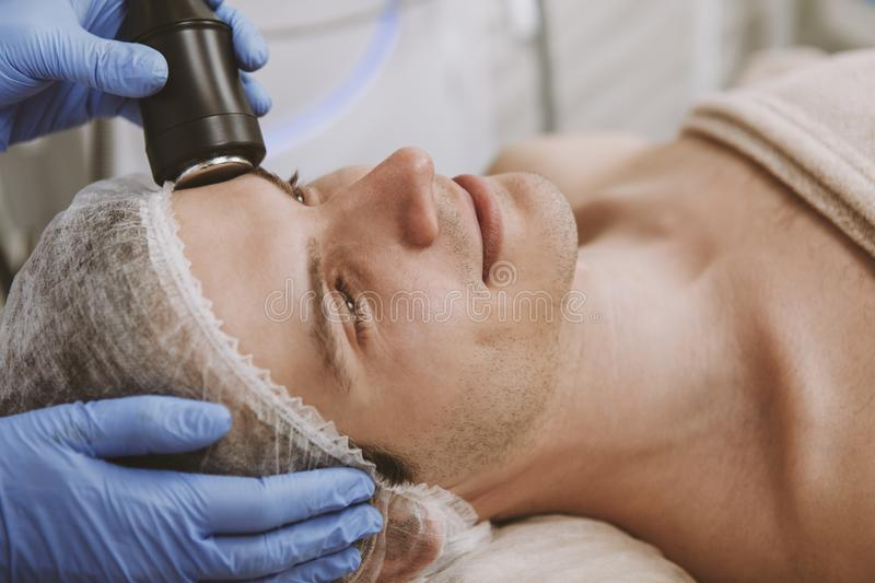 Handsome man getting facial skincare treatment stock photo
