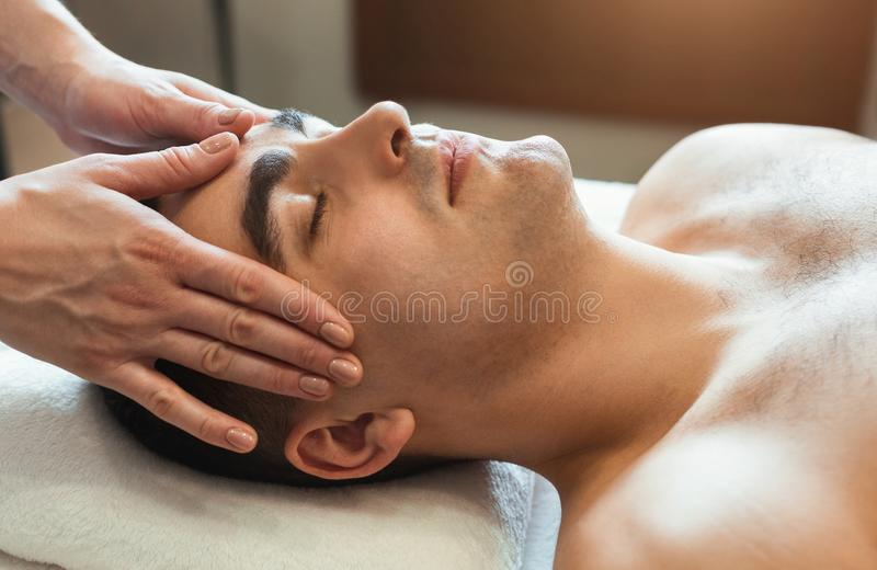 Handsome man getting professional face massage. In spa salon stock photos