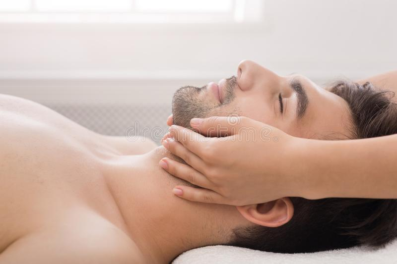Handsome man getting professional face massage in salon. Handsome man getting professional face massage in spa salon, side view royalty free stock image