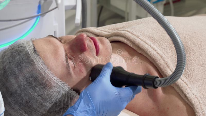 Handsome man getting rf-lifting treatment by cosmetologist stock photography