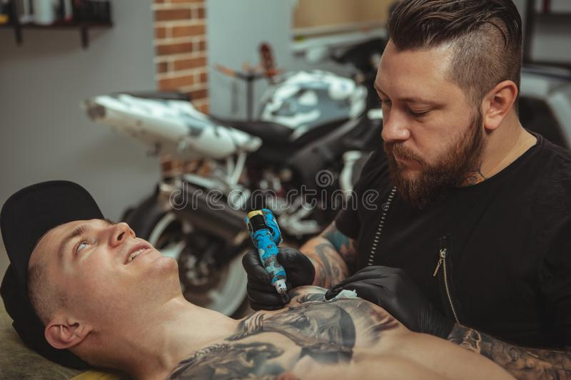 Handsome man getting a tattoo at alternative art studio stock photo