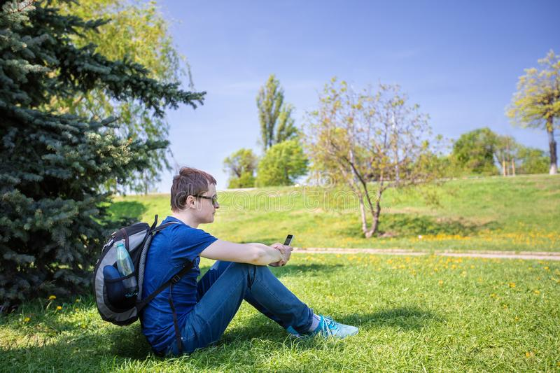 Handsome man on the grass with phone on a sunny day stock image
