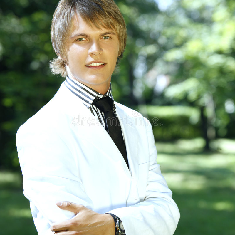 Handsome man with great smile and stripe top. Handsome man outdoors smiling in a white suit with stripe top and black tie stock photos