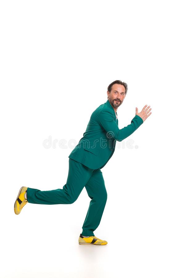 Handsome man in green suit. Imitating running stock images