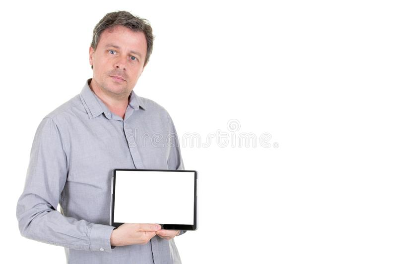 Handsome man in grey blue shirt isolated on white background demonstrating white empty blank screen of computer tablet royalty free stock images