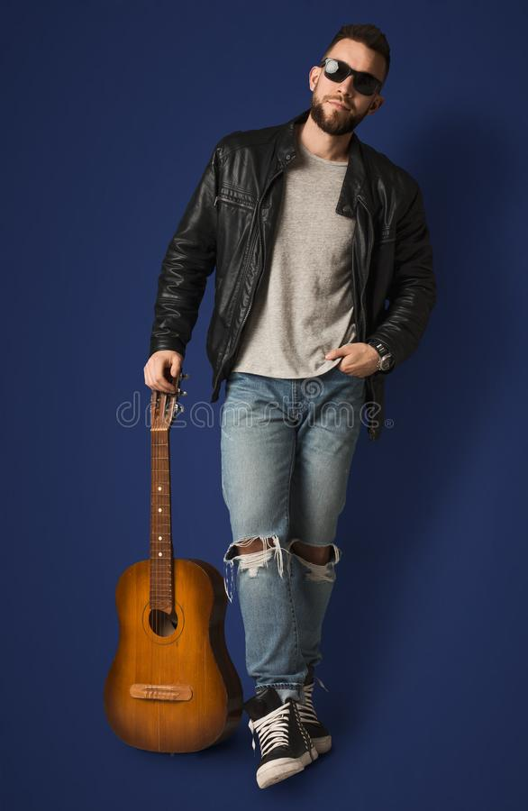 Handsome man with guitar posing in studio royalty free stock photo